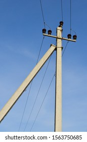 Corner reinforced concrete electric support. Electric pole with wires.