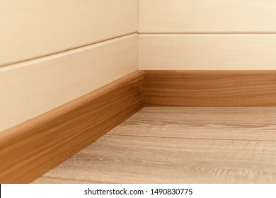 Corner of the room with walls, baseboards and natural wood floor