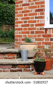 The corner of a set of stone and brick constructed steps leading to and from a garden patio area with various pots. Various seasonal plants grow in the pots.
