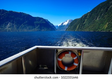 A corner of a ship with a life ring behind the back creates a waves along the lake of the mountains.