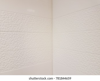 corner in shower in bathroom with white textured tiles