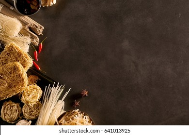 Corner and side border of Oriental noodles in a food still life with chili peppers and star anise, on a textured slate background with copy space