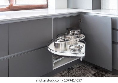 Corner storage mechanism called as magic corner, a perfect solution for pots and pans storage. Easy access for corner kitchen cabinets. Interior in a grey and white colors, grey soft touch matt fronts