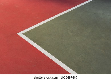Corner of a tennis field in daylight.