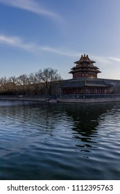 Corner tower of the surrounding walls of the Forbidden City seen across its moat on a spring evening in Beijing, China.