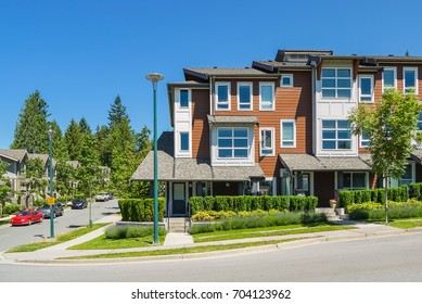 Corner unit of new townhouses with entrance door from the street on bright sunny day