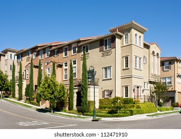 A corner view of a new multi-story townhome development in California.