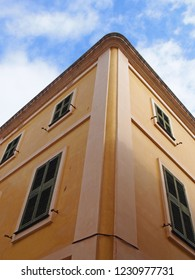 corner view of a typical menorcan spanish house painted yellow looking upwards with a blue summer sky and white clouds