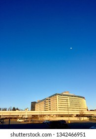 Tyson's Corner, Virginia- March 17, 2019: Early evening sunlight bathes Metro's Silver Line tracks (foreground) and an office building as the moon rises against a clear blue sky.