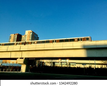 Tyson's Corner, Virginia- March 17, 2019: Early evening sunlight bathes a Metro Silver Line train on elevated tracks (foreground) and a luxury high-rise condominium building on a clear winter evening.