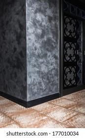 corner wall with textured Venetian plaster in the interior with black door