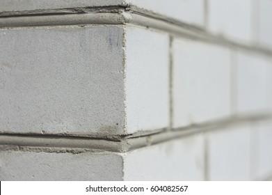 Corner of a white brick wall, close-up