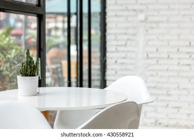 the corner of white room with table and chair