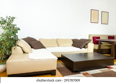 Corner  yellow sofa with colorful pillows and black wooden coffee table. Living room or interior with  modern and stylish design. Concept of contemporary home, indoor photo.