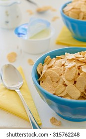 Cornflake cereals with greek yogurt in blue ceramic pot on the side with open yogurt and yellow napkins in background.