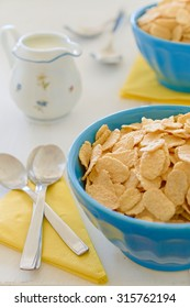 Cornflake cereals with milk in blue ceramic pot milk and yellow napkins in background.