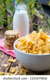 Cornflake cereals on white bowl with milk glass on table.