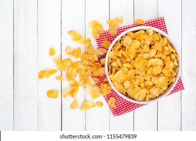 Cornflake cereals in white bowl on white wooden desk,Top view.