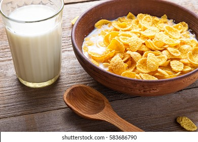 Cornflakes cereal and milk in a clay bowl. Morning breakfast.