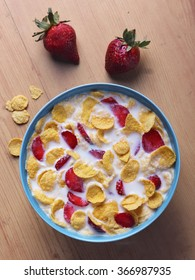 Cornflakes cereal and strawberry bowl for breakfast on blue bowl