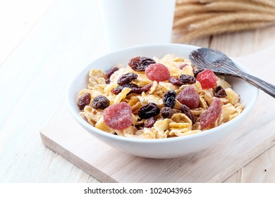 cornflakes and dry berry fruits in a white bowl on a wooden background.
