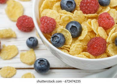 Cornflakes with fresh berries raspberry and blueberry in white bowl on the table. Healthy Breakfast. Selective focus. Top view