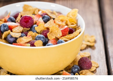 Cornflakes with fresh Strawberries, Raspberries and Blueberries on wooden background