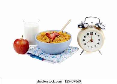 Cornflakes with fruits and alarm clock on the side