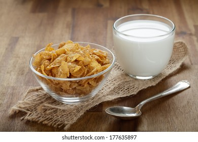 Cornflakes and milk on a wooden board