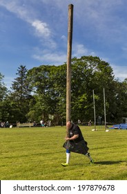 CORNHILL, ABERDEESNHIRE, SCOTLAND - 7 JUNE: This is man in the Tossing the Caber contest within the Cornhill Highland Games, Aberdeenshire, Scotland on 7 June 2014.