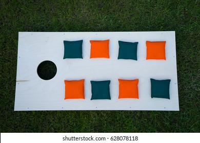 Cornhole Board Flat Lay with green and orange beanbags on grass