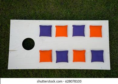 Cornhole Board Flat Lay with purple and orange beanbags on grass