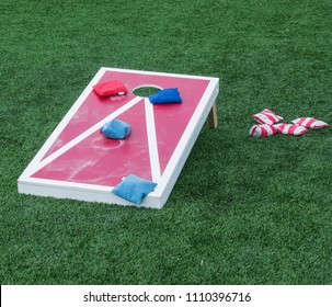 A cornhole board is set up with colorful beanbags resting on it after the competitiors have thrown them.