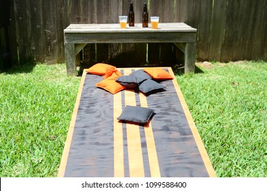 Cornhole lawn game with beer in background