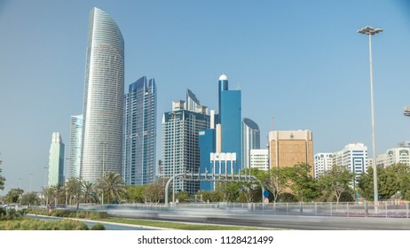 Corniche boulevard beach park along the coastline in Abu Dhabi timelapse with skyscrapers on background. Palms on a side. Blue sky at sunny day
