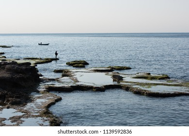 The Corniche street's seashore and fishermen fishing from the low tide rocks in Beirut, Lebanon