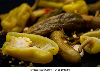 Cornichons (Mini French style Gherkin Cucumbers) and Pickled Pepperoncini Peppers on natural stone background.