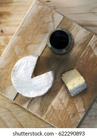 Cornish brie cheese and red wine - beautiful rustic, simple and plain natural wood background & cheeseboard. With lots of design / text space.