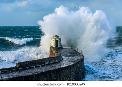 "A Cornish Harbour confronts gale force winds and swollen seas as waves crash into the ""Monkey Hut"" in Portreath."