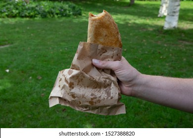 A Cornish pasty, with a bite taken out of it, in a brown paper bag
