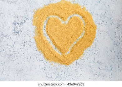 Cornmeal heart shape symbol over marble table. Top view. copy space.