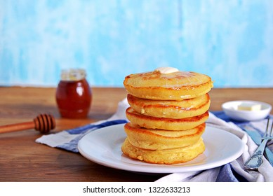 Cornmeal pancakes on a white plate. Served with butter and honey or maple syrup.
