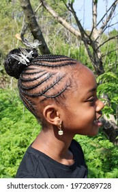 Cornrow Extensions Braided Into A Bun With Butterfly Hair Accessories  On Young African American Girl, Greenery In Background