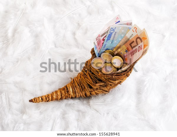 cornucopia - bills and change in a horn of plenty. horn is standing on a bed of feathers.