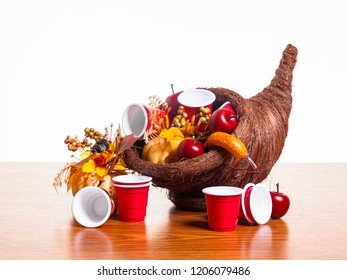 A cornucopia with decorative autumn harvest gourds and small red plastic beer cups. Thanksgiving.