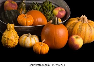 Cornucopia of fresh pumpkins, squash, apples and pomegranet isolated on black background