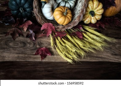 A cornucopia or horn of plenty spilling vegetables out on to a worn wooden harvest table. Colours are lightly faded.  Room for copy space.