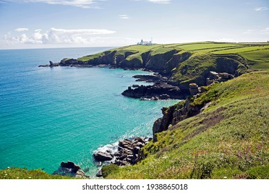 Cornwall, UK. Hiking on the South West Coast Path to Lizard Point. In the Foreground the Housel Bay, in the Background a little white Building, the Lizard Lighthouse.