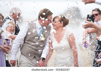 CORNWALL, UK - SEPTEMBER 6, 2016: Guests throw confetti over the bride and groom as they laugh and walk down the beach on their wedding day. Lusty Glaze Beach, Newquay.