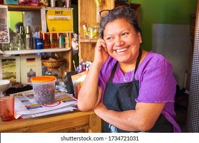 Coroico, La Paz / Bolivia - July 24 2016: Latin Brown Woman in a Purple Shirt an Apron Smiling in a Small Coffee Shop